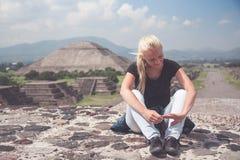 De vrouwenreiziger die op de bovenkant na lange hard rusten beklimt op één van beroemde ruïnes van oude stad Maya in Teotihuacan, stock foto
