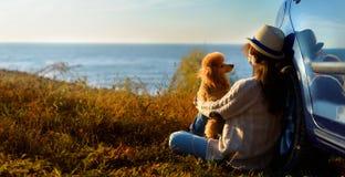 De vrouwenreiziger met hond geniet van mooie zonsondergang op overzees tijdens wegreis royalty-vrije stock foto's