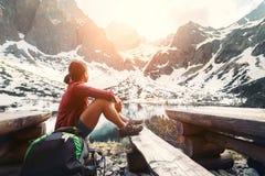 De vrouwenreiziger rust dichtbij bergmeer met mooie mening over s royalty-vrije stock afbeeldingen