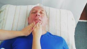 De vrouwenschoonheidsspecialist geeft man een stabiliserende gezichtsmassage in een kuuroordsalon stock videobeelden