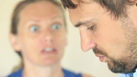 De vrouwenschreeuwen bij de man Het gezicht van een mens in profiel is close-up, is het vrouwen` s gezicht vaag stock video