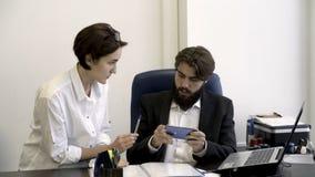 De vrouwensecretaresse toont belangrijke documenten aan haar gebaarde werkgever die met het spelen van smartphonespelen in het bu royalty-vrije stock afbeelding