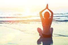 De vrouwensilhouet van de meditatieyoga op de achtergrond van het overzees en de verbazende zonsondergang Royalty-vrije Stock Foto's