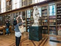 De vrouwentoerist breekt slimme telefoonfoto van British Museum-standbeeld Stock Foto