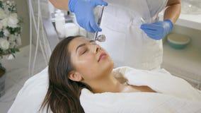 De vrouwenverjonging, glimlachend cliëntmeisje op procedures voedt en herstelt elk van lagenhuid in de Kosmetieksalon stock video