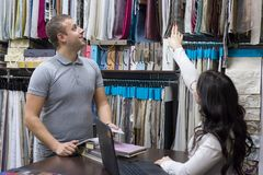 De vrouwenverkoper en een mannelijke klant in een stoffenopslag bekijken steekproeven van materialen stock foto