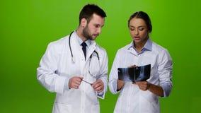 De vrouwenverpleegster raadpleegt een arts voor verdere behandelingspatiënt stock footage