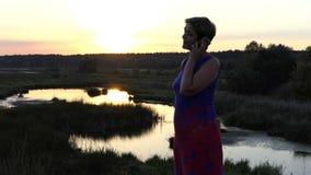De vrouwenvraag van Nice op een meerbank bij zonsondergang stock videobeelden