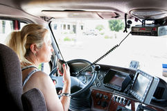 De vrouwenvrachtwagenchauffeur die van de blonde op haar radio spreekt. Stock Afbeeldingen