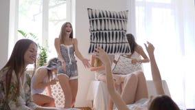De vrouwenvrienden die met hoofdkussens vechten, actieve meisjes hebben pret en het lachen op bed bij weekend stock videobeelden
