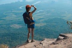 De vrouwenwandelaar geniet van de mening over de bovenkant van de klippenrand van berg Royalty-vrije Stock Foto's