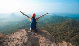 De vrouwenwandelaar geniet van de mening over de bovenkant van de klippenrand van berg Royalty-vrije Stock Afbeeldingen