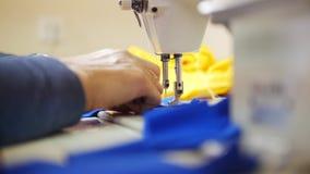 De vrouwenwerken met doek op naaimachine Nadruk op textiel stock video