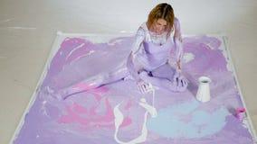 De vrouwenyogi in purpere verf zit op een geschilderd canvas stock video