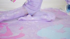 De vrouwenyogi in purpere verf zit op een geschilderd canvas stock footage