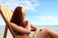 De vrouwenzitting bij het strand u zette het zonnescherm Stock Afbeeldingen