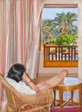 De vrouwenzitting bij het venster en bewondert exotische aard royalty-vrije stock foto