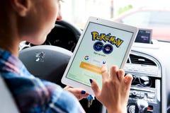 De vrouwenzitting in een auto en het spelen van een Pokemon gaan spel Stock Foto