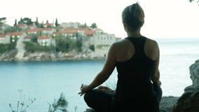 De vrouwenzitting in lotusbloem stelt op de achtergrond van de stad en het overzees stock video