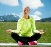 De vrouwenzitting in lotusbloem stelt in openlucht het doen van yoga stock afbeelding