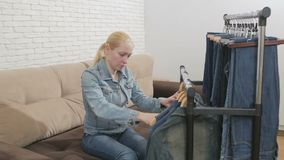 De vrouwenzitting op een bank onderzoekt een inzameling van denimkleren die op een hanger hangen stock videobeelden