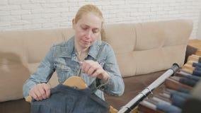 De vrouwenzitting op een bank onderzoekt een inzameling van denimkleren die op een hanger hangen stock video