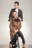 De vrouwenzitting op een kruk, haar vriend bevindt zich erachter Royalty-vrije Stock Foto