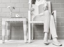 De vrouwenzitting op houten weefselstoel binnenshuis voor het lezen van een wit boek in vrije tijd in de middag, ontspant tijd en stock fotografie