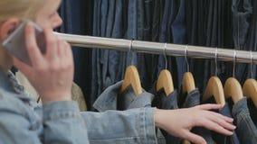 De vrouwenzitting op de laag spreekt op de telefoon en inspecteert een inzameling van jeans die op de hanger hangen stock videobeelden