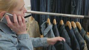 De vrouwenzitting op de laag spreekt op de telefoon en inspecteert een inzameling van jeans die op de hanger hangen stock footage