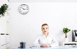 De vrouwenzitting van de blonde in haar bureau. Stock Foto's
