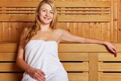 De vrouwenzitting van de blonde in sauna Royalty-vrije Stock Afbeeldingen