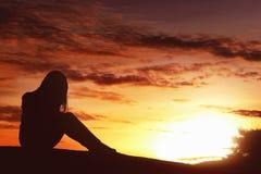 De vrouwenzitting van de silhouet droevige uitdrukking alleen bovenop de heuvel stock foto's