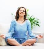 De vrouwenzitting in Yoga stelt royalty-vrije stock afbeelding