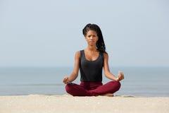 De vrouwenzitting in yogalotusbloem stelt Royalty-vrije Stock Afbeeldingen