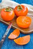 De vruchten van de besnoeiingsdadelpruim op houten verticale raad en lijst, Stock Foto