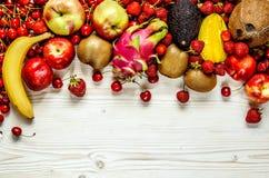 De vruchten van kers, aardbei, banaan, avocado, carom, kokosnoot, perzik, appel en draakfruit liggen op een witte houten oppervla stock fotografie