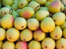 De vruchten van peren die in een rij op markt worden gestapeld Stock Foto