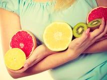 De vruchten van de vrouwenholding kiwi Sinaasappel, citroen en grapefruit stock afbeeldingen