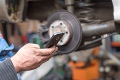 De vuile arbeidershanden gebruiken een smartphone stock foto