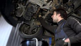 De vuile autowerktuigkundige schroeft versleten oliefilter onder opgeheven auto los tijdens onderhoud stock videobeelden
