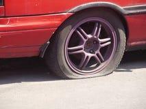 De vuile oude rode gelaten leeglopen onderbreking van de autoband Stock Afbeelding