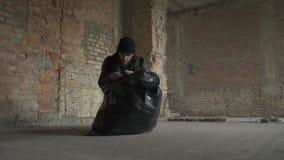 De vuile slechte daklozen vinden telefoon in vuilniszak stock videobeelden