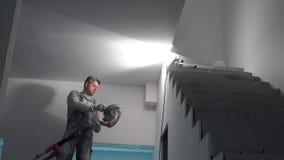 De vuile stukadoormens poetst plafond met schuurmachine op Huisvernieuwing stock video