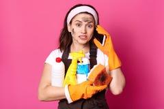 De vuile uitgeputte huisvrouw houdt veel het schoonmaken van vloeistoffen in handen, die over telefoon spreken, aandachtig luiste stock afbeeldingen