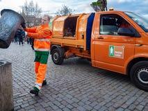 De vuilnisman giet huisvuil in de vuilnisauto stock afbeeldingen