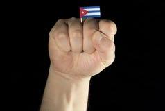 De vuist van de mensenhand met Cubaanse vlag die op zwarte achtergrond wordt geïsoleerd Stock Foto