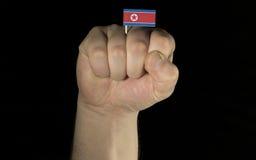 De vuist van de mensenhand met het Noorden Koreaanse die vlag op zwarte wordt geïsoleerd Stock Foto