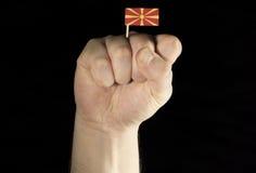 De vuist van de mensenhand met Macedonische vlag die op zwarte achtergrond wordt geïsoleerd Royalty-vrije Stock Foto's