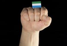 De vuist van de mensenhand met Sierra Leonevlag op zwarte wordt geïsoleerd die Stock Foto